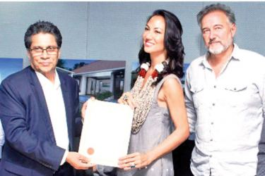 US based investors, Dale and Sabrina exchanging the agreement with BOI Chairman Mangala Yapa. Picture by Sulochanga Gamage
