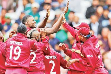 West Indies` captain Jason Holder celebrates with team mates after taking the wicket of his rival Pakistan captain Sarfaraz Ahmed.