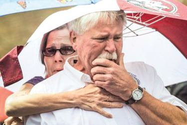 Frank Janes is comforted by his wife, Cathie Janes, during the prayer vigil at Strawbridge Marketplace in response to a shooting at a municipal building in Virginia Beach, Virginia on Saturday.