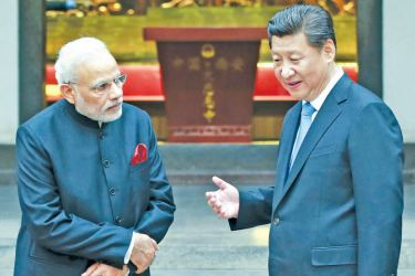 Chinese President Xi Jinping (R), speaks to Indian Prime Minister Narendra Modi during a visit to a Buddhist Temple in Xian, Shaanxi Province.