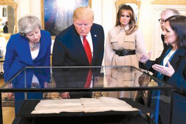 British Prime Minister Theresa May, US President Donald J. Trump and his wife Melania Trump look on an historic document during a meeting at 10 Downing street in London, Britain  on Tuesday.