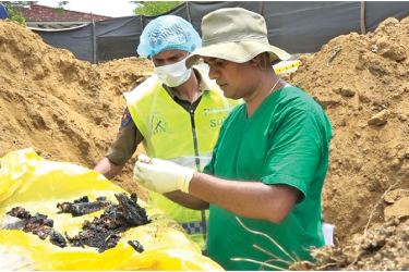 Police and Judicial Medical Officers inspecting bone fragments.(Inset): Ampara Additional Magistrate Asanga Hettiarachchi at the scene.  Pictures by Chandana Liyanaarachchi