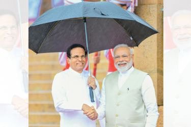 BRAVING THE WEATHER TOGETHER : President Maithripala Sirisena holds the umbrella for Indian Prime Minister Narendra Modi at the welcoming ceremony at the Presidential Secretariat, where the Indian PM was accorded a Guard of Honour yesterday. Picture by Sudath Silva