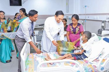 Health Minister Dr. Rajitha Senaratne presents a gift package to a child at Jaffna Teaching Hospital.