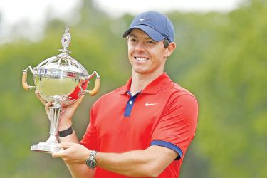 Rory McIlroy of Northern Ireland poses for a photo with the trophy after winning the RBC Canadian Open at Hamilton Golf and Country Club on June 09. AFP