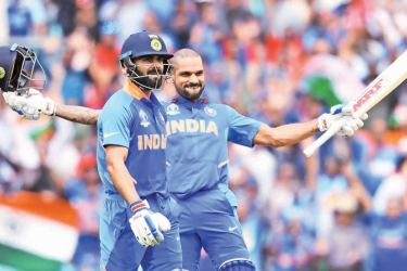 India's Shikhar Dhawan (R) celebrates after scoring a century (100 runs) alongside India's captain Virat Kohliduring the 2019 Cricket World Cup group stage match between India and Australia at The Oval in London on June 9. AFP