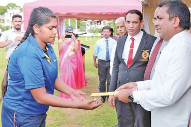 Education Minister Akila Viraj Kariyawasam hands over an appointment letter to an instructor.