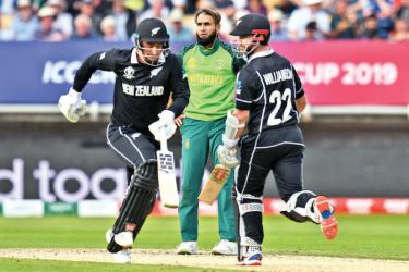 New Zealand's captain Kane Williamson (R) and New Zealand's Colin de Grandhomme (L) run between the wicket off the bowling of South Africa's Imran Tahir (C) during the 2019 Cricket World Cup group stage match between New Zealand and South Africa at Edgbaston in Birmingham, central England, on June 19. AFP