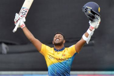 Avishka Fernando soaks in the applause after reaching his maiden ODI century in the World Cup match against West Indies at Chester-le-Street, Durham on Monday. Pix by Kamal Jaymanna