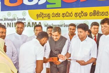 Housing and Construction and Cultural Affairs Minister Sajith Premadasa and Acting Indian High Commissioner Dr. Shilpak Ambule handing over the deeds of the houses.