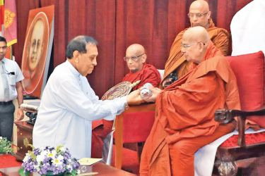 Speaker Karu Jayasuriya receiving the honorary title from the Mahanayake of Amarapura Nikaya Most Ven Kotugoda Dhammawasa Thera. Picture by Saliya Rupasinghe