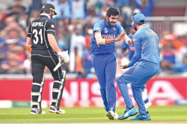 India's Jasprit Bumrah removes New Zealand opener Martin Guptill for one and is congratulated by team mate KL Rahul in the World Cup semi-final at Old Trafford on Tuesday. – AFP