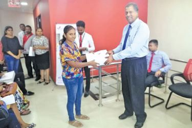 DFCC  Vice President/Regional Manager  Candiah Jegarajah  handing over study packs to students in Ampara