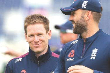 England's captain Eoin Morgan (L) laughs with teammate Liam Plunkett during a training session. - AFP