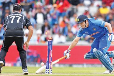 The defining moment of the game India's MS Dhoni is run out by a direct throw from New Zealand's Martin Guptill (not in picture) for 50 in the first World Cup semi-final played at Old Trafford, Manchester on Wednesday. – AFP