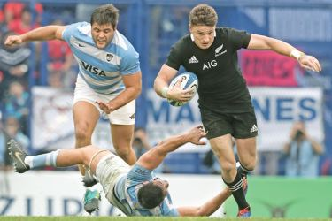 New Zealand's All Blacks fly half Beauden Barrett (R) runs with the ball past Argentina's Los Pumas flanker Pablo Matera (C) during their Rugby Championship match played at Jose Amalfitani stadium in Buenos Aires, Argentina on Saturday. - AFP