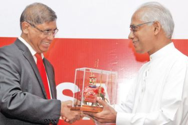 CA Sri Lanka President Jagath Perera presents a token of appreciation to Minister Wickramaratne at the event. Picture by Roshan Pitipana