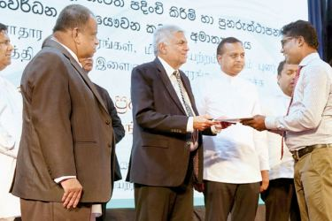 Prime Minister Ranil Wickremesinghe presenting an appointment to a graduate during the first stage of a programme to absorb 16,800 graduates into the public service. The ceremony was held at Temple Trees yesterday. Picture by Hirantha Gunathilaka