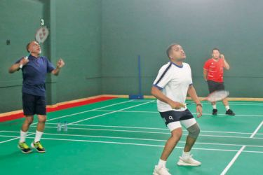 Sport Minister Harin Fernando taking part in an exhibition match along with Sri Lanka Badminton (SLB) President Rohan de Silva, during the opening ceremony of the revamped court complex at the SLB Headquarters in Colombo 7 on Thursday.