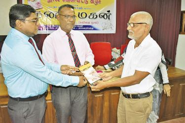 Assistant Education Director M.A. Abuthahir receiving a copy of the book from the chief guests. Picture by I.L.M. Rizan, Addalaichenai Central Corr.
