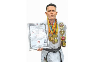Shehan Wijerathna with his medals  and black belt certificate.