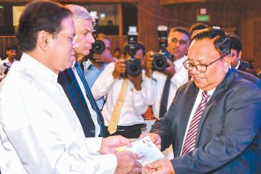 Minister of Postal Services & Muslim Religious Affairs Abdul Haleem hands over a first day cover to President to commemorate the BOC 80th anniversary celebrations.