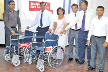 Transport Terminal officer Thanuja Prasad Peris receiving Wheel Chairs from HelpAge Executive Director Samantha Liyanawaduge. HelpAge officials Ananda  Kannangara, Nelum Ekanayaka and  Buddhika Nanayakkara are also in the picture.