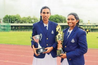 Here the victorious captains of Elle team of Wadduwa Central Ishini Mendis (on left) and cricket team Chamini Nirasha (on right) holding their championship cups, soon after the Awards Ceremony at the Sugathadasa Indoor Stadium.