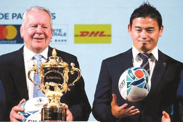 Japan's rugby player Ayumu Goromaru (right) looks at the Webb Ellis Cup next to World Rugby Chairman Bill Beaumont.