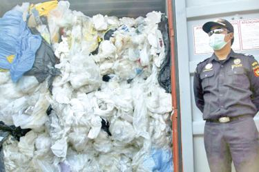 An Indonesian officer opens a container filled with illegal imported plastics waste in Batam on Monday.