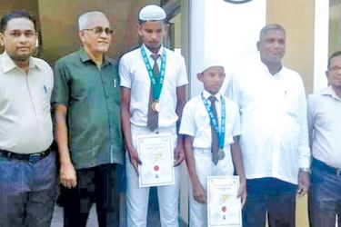 Victorious athletes  of Addalaichenai National School with principals and their medals and certificates.