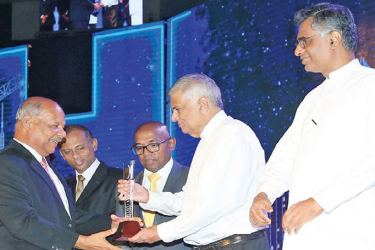 Prime Minister Ranil Wickremesinghe presenting a token of appreciation while Minister Patali Ranawaka looks on. (Picture by PM's Media Division)