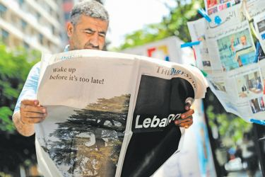 "A man checks a copy of the Lebanese local English-language newspaper  ""The Daily Star"" in the capital Beirut on Thursday, which refrained from publishing news articles in its print edition in protest against the  ""deteriorating situation"" in Lebanon. - AFP"