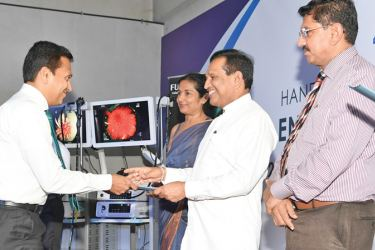 Health Minister Dr. Rajitha Senaratne hands over an endoscopy machine to hospital authorities, while Health Services Director General Dr. Anil Jasinghe and Health Secretary Wasantha Perera look on.