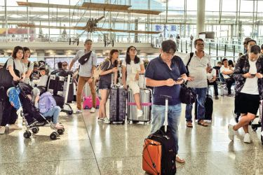 Passengers look at an electric board to check their flights status in the departures area of Hong Kong's international airport yesterday, the day after the airport closed due to pro-democracy protests. - AFP
