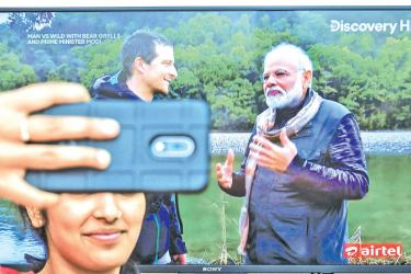 A fan takes a selfie while watching on television the special edition of 'Man Vs Wild' series hosted by survival expert Bear Grylls (L), going on a mission with Indian Prime Minister Narendra Modi, in Bangalore on Monday. - AFP