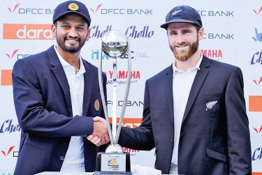 Captains Dimuth Karunaratne and Kane Williamson shake hands in front of the DFCC Bank Cup for which the two-Test series between Sri Lanka and New Zealand will be played for. The first Test began at Galle International Stadium yesterday. Pic Nathan Delight