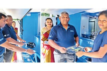 Opening of the new Bank on Wheels unit by Commercial Bank's Assistant General Manager Personal Banking and SME Delakshan Hettiarachchi and Regional Manager Uva Sabaragamuwa Region Elmo Sooriyaarachchi accepts  a deposit from a customer.