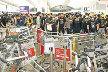 Pro-democracy protestors block the entrance to the airport terminals after a scuffle with police at Hong Kong's international airport late on Tuesday. - AFP