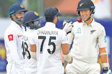An unusual incident as the ball gets stuck in the helmet of New Zealand batsman Trent Boult (R) during the second day of the first Test at the Galle International Cricket Stadium yesterday. Sri Lankan wicket-keeper Niroshan Dickwella (2L) and Dhananjaya de Silva (2R) look on. – AFP