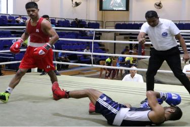 The referee begins the count after P.V.D.D. Saparamadu (Slimline) floors N.H. Thilakarathna (Navy) in the second round of the Light Welter weight bout.