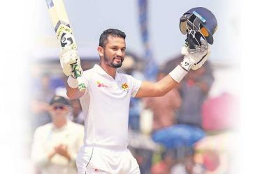 Sri Lanka captain Dimuth Karunaratne celebrates his century on the fifth and final day of the first cricket Test at the Galle International Stadium yesterday. – AFP
