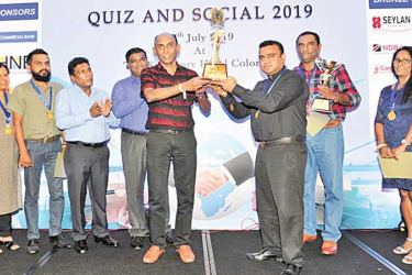 People's Bank CEO/General Manager Rasitha Gunawardana presenting the Challenge Trophy to the Hatton National Bank A team.