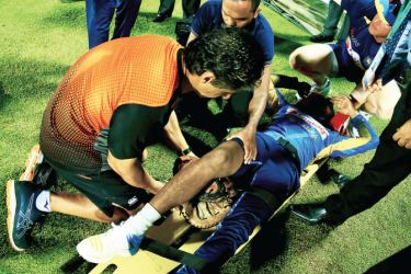 Sri Lanka cricketer Kusal Mendis is attended to on the field by former Sri Lanka and current New Zealand physio Tommy Simsek (orange T-shirt) after injuring his right knee during the second T20I against New Zealand at the Pallekele International Stadium on Tuesday. Picture by Nathan Delight