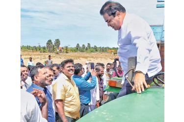 Minister P. Harrison alights after testing a farmer's tractor in Mannar, while Minister Rishad Bathiudeen and farmers look on.
