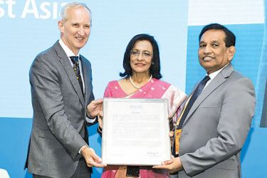 Health Minister Dr. Rajitha Senaratne receives the certificate from WHO Regional Director for South East Asia Dr. Poonam Khetrapal Singh and an official.