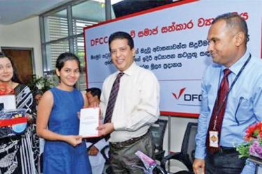 DFCC Bank CEO Lakshman Silva presents a donation to a student. Vice President Marketing, Nilmini Gunaratne and Vice President/Regional Manager, Wajira Punchihewa are also in the picture .
