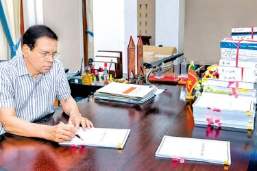 President Maithripala Sirisena yesterday signing documents related to the extradition of former Central Bank Governor Arjuna Mahendran from Singapore to Sri Lanka. Picture by Udesh Gunaratne - President's Media Division