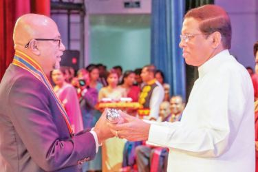 Dian Gomes receiving the Presidential honorary Award SRI LANKA SIKHAMANI from President Maithripala Sirisena at the 'National Honours' ceremony.