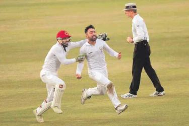 Afghanistan captain Rashid Khan sets off on a celebratory run, with Afsar Zazai in pursuit, after the last Bangladesh wicket had fallen in the inaugural one-off Test played at Chattogram on Monday. Rashid finished with a match bag of eleven wickets..